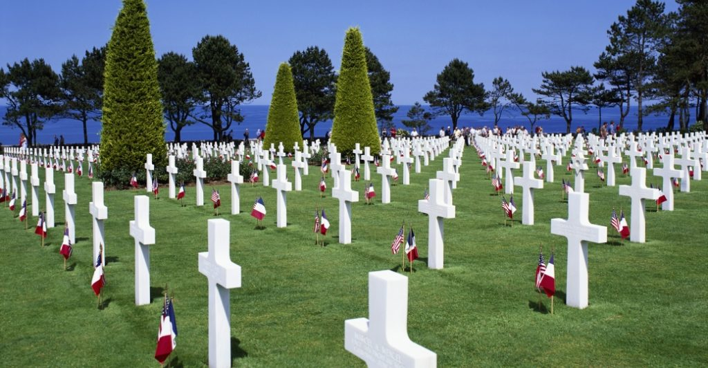 The Normandy American Cemetery and Memorial in France is located in Colleville-sur-Mer, on the site of the temporary American St. Laurent Cemetery, established by the U.S. First Army on June 8, 1944 as the first American cemetery on European soil in World War II. The cemetery site, at the north end of its half mile access road, covers 172.5 acres and contains the graves of 9,387 of our military dead, most of whom lost their lives in the D-Day landings and ensuing operations. On the Walls of the Missing, in a semicircular garden on the east side of the memorial, are inscribed 1,557 names. Rosettes mark the names of those since recovered and identified.